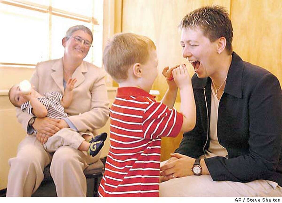 Sherri Kokx, right, pretends to bite while enjoying a light moment with her biological son, Zachary Bender-Kokx, 3, as Kokx's partner of three years Johanna Bender looks on while holding her biological son, Quintin Bender-Kokx following a news conference Wednesday, Aug. 4, 2004, at The Moutaineers club in Seattle. Gay couples can be married under Washington state law, because denying their right to do so is a violation of their constitutional rights, King County Superior Court Judge William L. Downing ruled Wednesday. (AP Photo/Steve Shelton) Ran on: 08-05-2004 Sherri Kokx (right) plays with her biological son, Zachary Bender-Kokx, 3; her partner of three years, Johanna Bender, holds her biological son, Quintin Bender-Kokx, after a news conference. Ran on: 08-05-2004