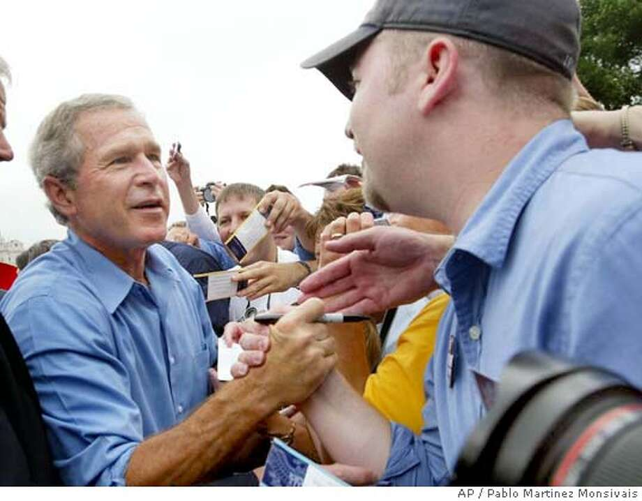 President Bush shakes hands with supporters at a campaign rally at LeClaire Park Bandshell in Davenport, Iowa Wednesday, Aug. 4, 2004. Bush is campaigning in two adjoining Midwest states he narrowly lost four years ago, as he and rival John Kerry battle it out in the same Iowa city on the same day. (AP Photo/Pablo Martinez Monsivais) Photo: PABLO MARTINEZ MONSIVAIS