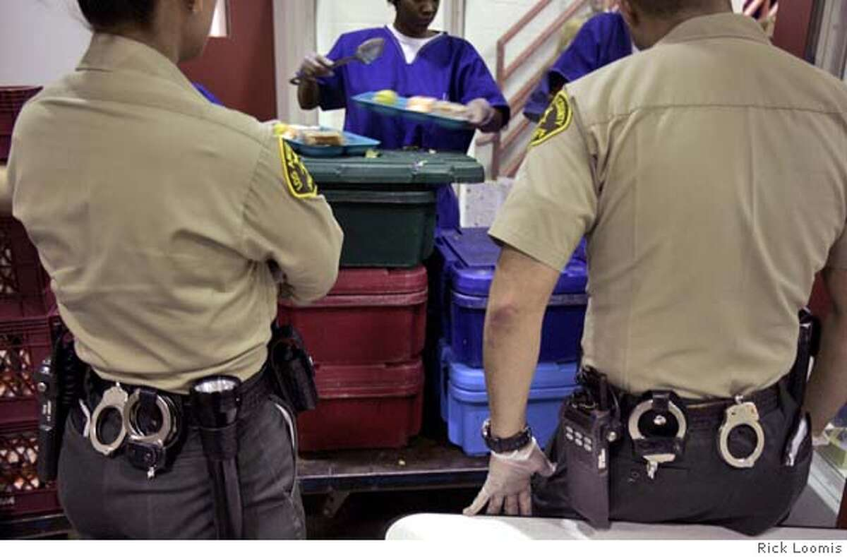TIME TO EAT: Two Los Angeles County sheriff's deputies keep watch as inmates pass out meals to fellow prisoners. The biggest security problem is pruno, an alcoholic beverage inmates make. Rick Loomis -- 089653.ME.1110.food.7.RL--Los Angeles, Ca.--Two Los Angeles County Sheriffs watch over inmates at the Los Angeles County Jail Ias meals are passed out ot other inmates. Thousands of meals are prepared and served by inmates to other inmates in the facility.