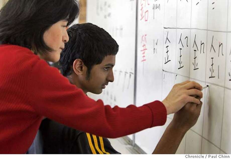 chineseschool_038_pc.jpg  Sunny Yu helps Chethan Kosaraju (cq) write chinese characters on the board. A beginning Mandarin language class taught by Sunny Yu at Piedmont High School on 12/16/04 in Piedmont, CA. PAUL CHINN/The Chronicle MANDATORY CREDIT FOR PHOTOG AND S.F. CHRONICLE/ - MAGS OUT Photo: PAUL CHINN