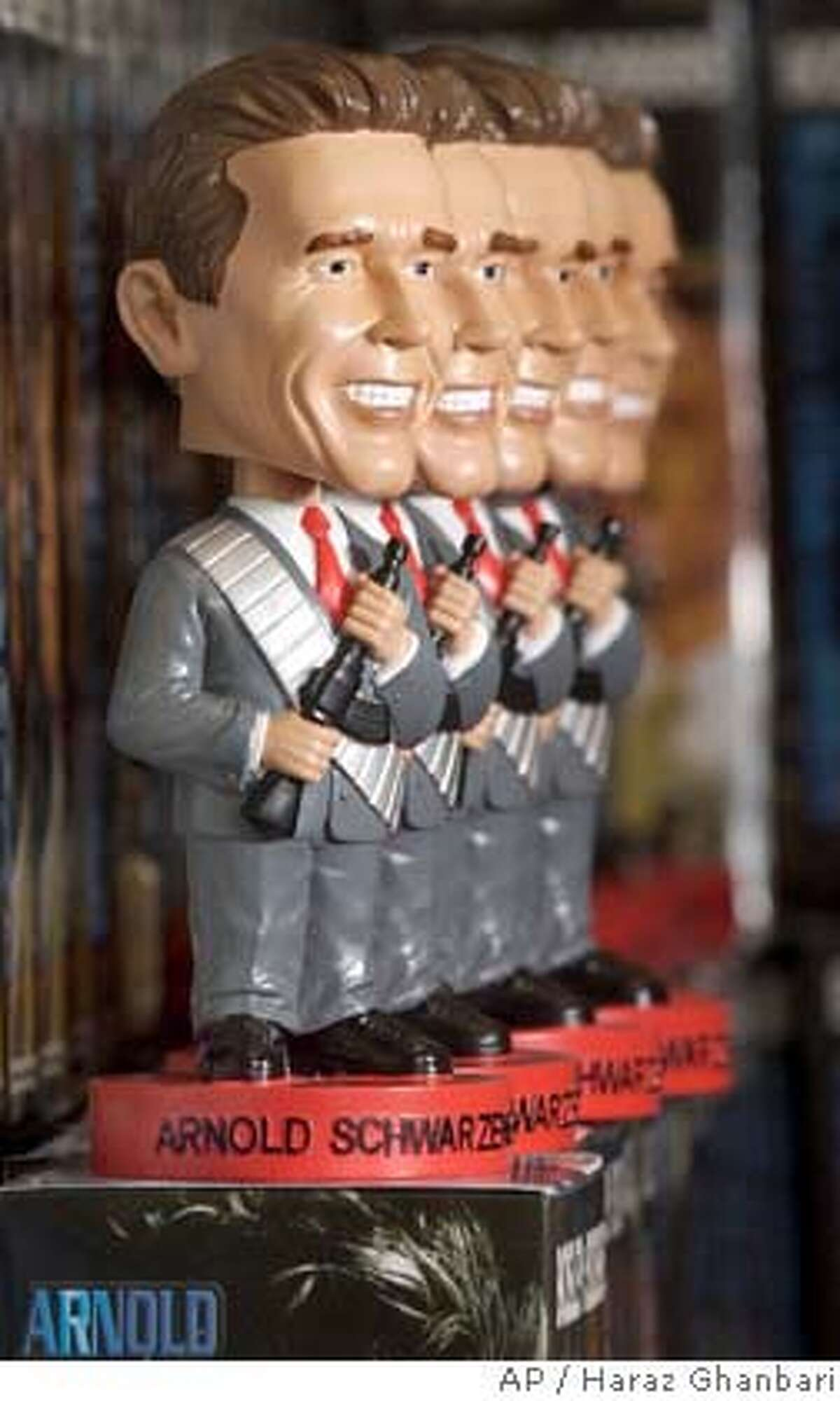 ** FILE ** A row of bobblehead dolls featuring the name and likeness of Calif. Gov. Arnold Schwarzenegger wearing a business suit and holding a gun are pictured in an office at Ohio Discount Merchandise in this April 30, 2004, file photo in Canton, Ohio. Schwarzenegger announced Monday, Aug. 2, 2004, that he had settled a suit with Ohio Discount Merchandise Inc. allowing them to produce the doll without the gun, and Ohio Discount also agreed to donate a portion of its sales to Schwarzenegger's nonprofit organization, Arnold All-Stars afterschool program. (AP Photo/ Haraz Ghanbari) APRIL 20 2004 FILE PHOTO