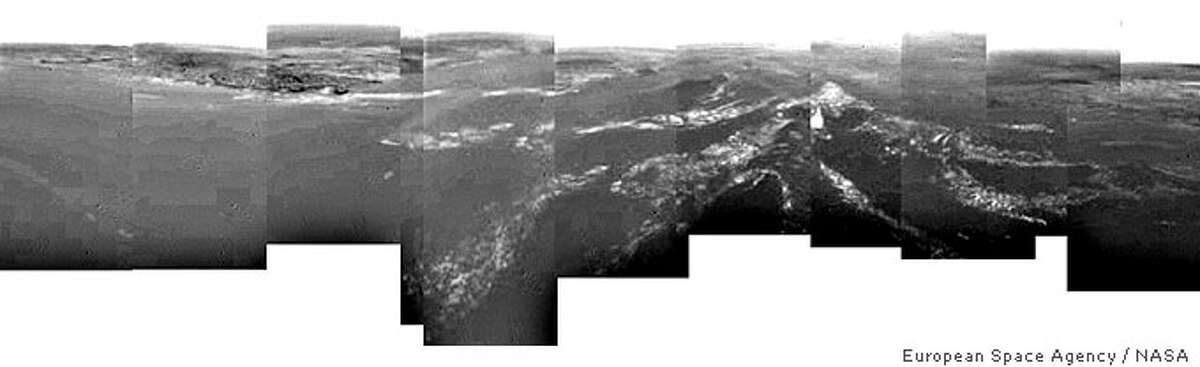 A composite picture produced from images returned January 14, 2005 by the European Space Agency's (ESA) Huygens probe, during its successful descent to land on Titan, shows a full 360-degree view around Huygens. The left-hand side, behind the space probe shows a boundary between light and dark areas. The white streaks seen near this boundary could be ground 'fog', as they were not immediately visible from higher altitudes. As the probe descended, it drifted over a plateau (center of image) and was heading towards its landing site in a dark area (right). From the drift of the probe, the wind speed has been estimated at around 6-7 kms per hour. These images were taken from an altitude of about 8 kms and a resolution of about 20 meters per pixel. NO ARCHIVES REUTERS/ESA/NASA/University of Arizona BLACK AND WHITE ONLY QUALITY FROM SOURCE