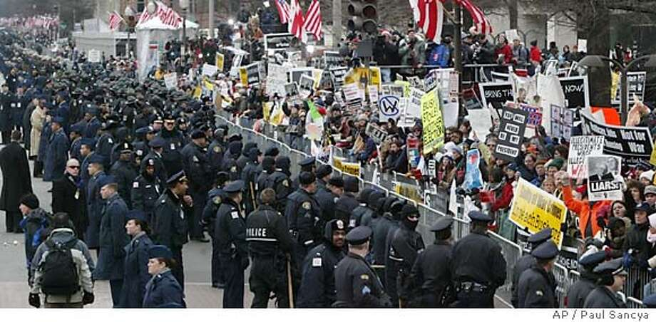 Barricades and a heavy security lineup separates demonstrators from the inaugural parade along the route to the White House from the Capitol in Washington Thursday, Jan. 20, 2005. (AP Photo/Paul Sancya) Photo: Paul Sancya
