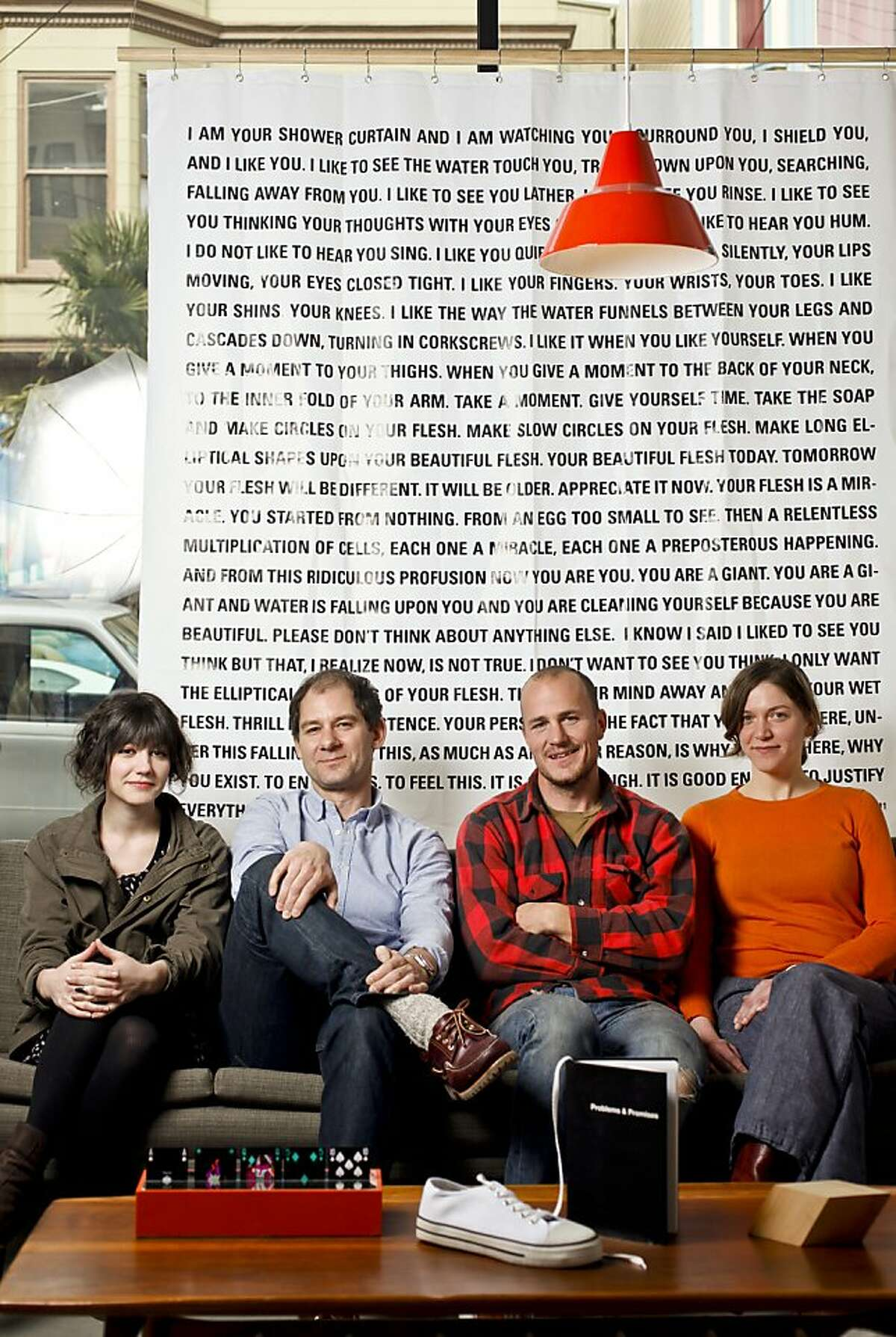 """Assistant editor Caitlin Kirkpatrick, Editors Jonn Herschend and Will Rogan, and intern Genessa Keahola of, """"The Thing Quarterly,"""" are seen in their Mission District office on Wednesday, Jan. 18, 2012 in front of Dave Eggers' issue 16 shower curtain."""