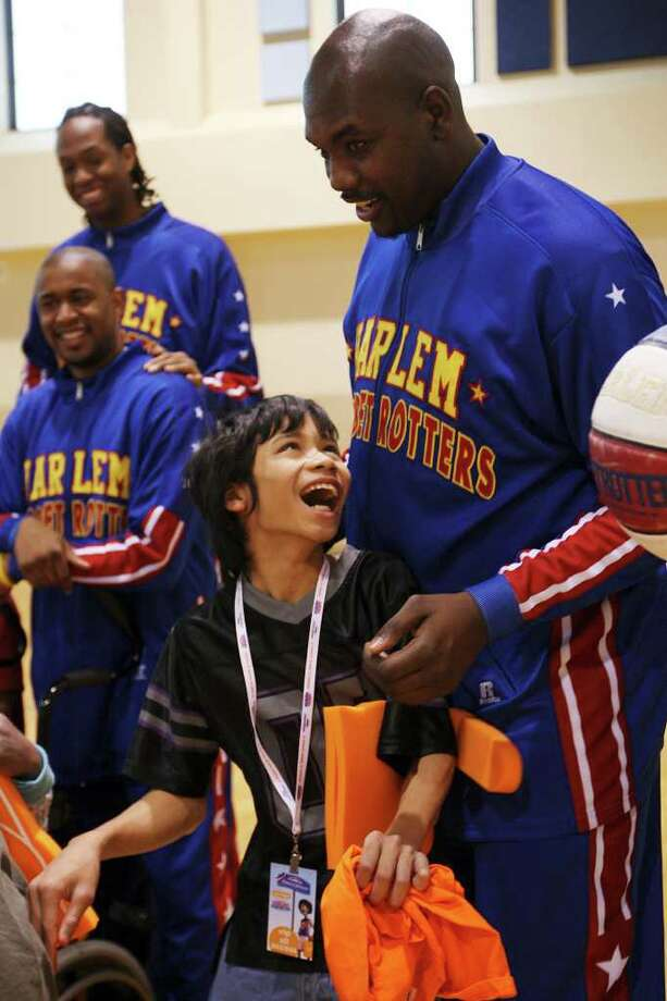 Ethan Lambert gets ready to have his picture taken with the Harlem Globetrotters' Big Easy Lofton (right). The event benefited the Starlight Children's Foundation, which supports children with life-threatening or chronic illnesses and their families. / © San Antonio Express-News