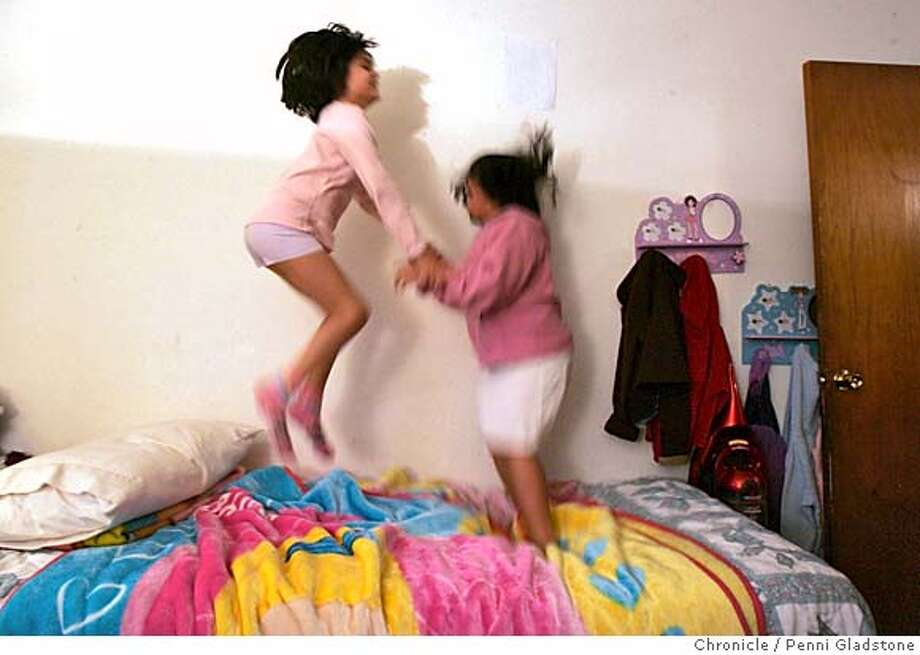EPILEPSY315PG.JPG  just before bedtime, Paola at left jumps with her sister Niki on Niki's bed.  eight-year-old Paola First diagnosed with epileptic seizures four years ago, at school and home and at hospital. Under the supervision of Donald Olson, MD, director of pediatric epilepsy at LPCH, Paola has been able to reduce her seizures via medication from around 50 a day to 10 or so when times are good. Silvia Humildad is the mom.t Monterey Park School then at home.  The San Francisco Chronicle, Penni Gladstone  Photo taken on 1/12/05, in Salinas, Photo: Penni Gladstone