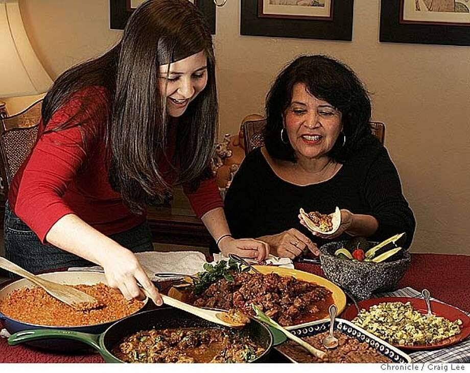 "Rent-a-Grandma food story with a Mexican pair: ""Grandma"" Juliana Gutierrez (right) and ""grandaughter"" Christina Noz (left). They first go grocery shopping at Chavez Supermarket in Menlo Park and then cook at Juliana's apartment in Los Gatos. In this photo, they are now enjoying the dishes they just cooked.  Event on 1/6/05 in Menlo Park. Craig Lee / The Chronicle Photo: Craig Lee"