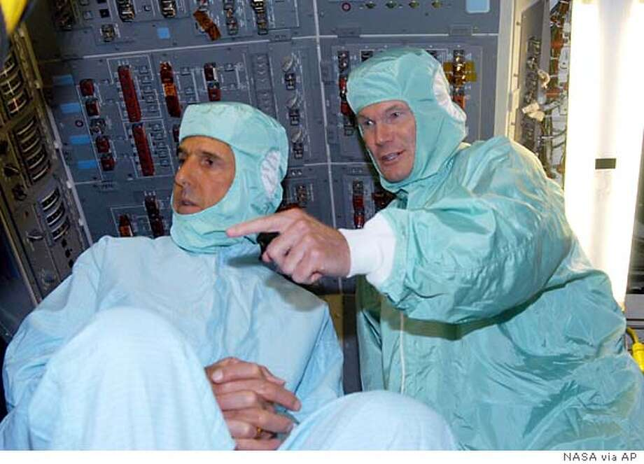 Democratic presidential candidate Sen. John F. , D-Mass., left, and Sen. Bill Nelson, D-Fla., dressed in clean room attire, visit the flight deck of Space Shuttle Discovery during a tour of the Orbiter Processing Facility, Monday, July 26, 2004 at Kennedy Space Center in Cape Canaveral, Fla. The suits are required dress to board Discovery, currently being prepared for flight on the next Space Shuttle mission. (AP Photo/ NASA)