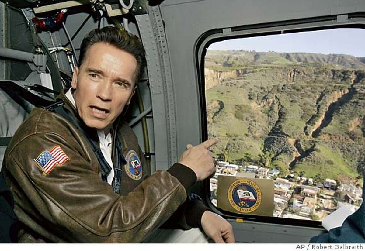 California Gov. Arnold Schwarzenegger talks during a helicopter tour Wednesday, Jan. 12, 2005, over the site of Monday's hillside collapse that buried houses under tons of mud and debris in La Conchita, Calif. (AP Photo/Robert Galbraith, Pool) POOL PHOTO