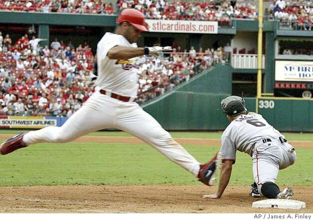 St. Louis Cardinals Albert Pujols leaps for first base while San Francisco Giants J.T. Snow makes the tag for the out during the eleventh inning of their baseball game in St. Louis Saturday, July 24, 2004. The Giants defeated the Cardinals by the final score of 5-3 in eleven innings. (AP Photo/James A. Finley) Photo: JAMES A. FINLEY