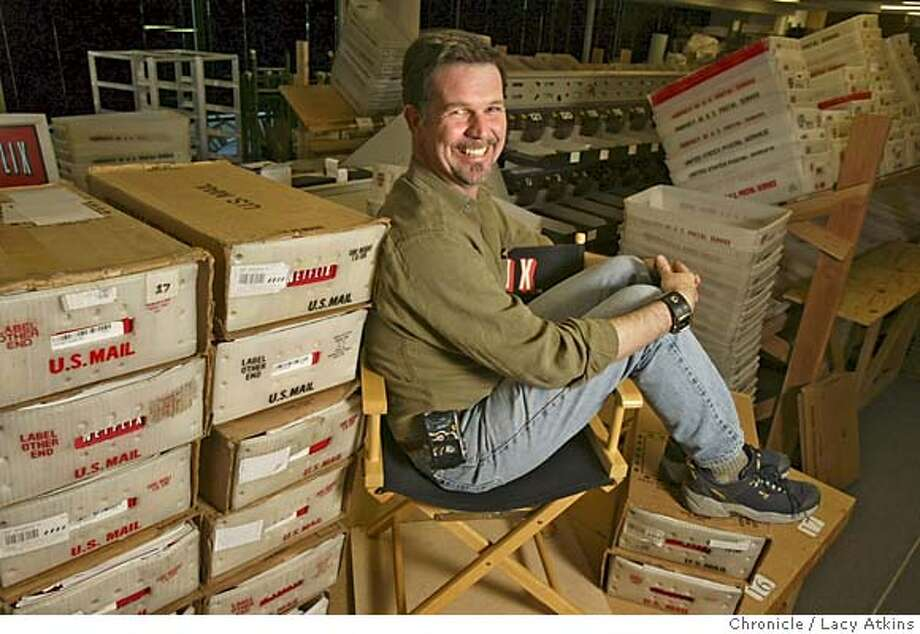 NETFLIX008.JPG  Reed Hastings, Netflix's chief executive sits among boxes filled with DVDs that are being mailed out to customers, Tuesday March 2 , 2004, in San Jose Event on 3/2/04 in SAN JOSE. LACY ATKINS / The Chronicle Netflix envelopes go along a conveyor belt, above, at the company's San Jose distribution center. Reed Hastings, left, gambled on the new DVD format when he founded Netflix in 1997. MANDATORY CREDIT FOR PHOTOG AND SF CHRONICLE/ -MAGS OUT Photo: LACY ATKINS