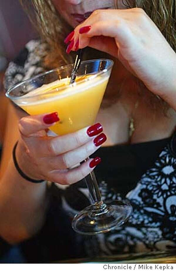 A happy hour goer drinks an Elephant Bar special called a Raspberry E-Bartini.  The Elephant Bar in Burlingame is a popular happy hour spot.  MIKE KEPKA/The Chronicle Photo: MIKE KEPKA