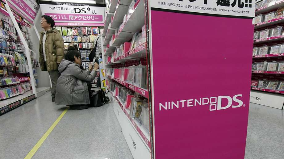 Shoppers select Nintendo video game software at an electronics retailer in Tokyo Thursday, Jan. 26, 2012. Nintendo Co. sank into losses for the April-December period last year, battered by a price cut for its 3DS handheld machine and a strong yen that eroded earnings. The Japanese video game machine maker behind Super Mario and Pokemon franchises reported Thursday a loss of 48.35 billion yen ($627.9 million) for the first nine months of the fiscal year ending March 2012. (AP Photo/Koji Sasahara) Photo: Koji Sasahara, Associated Press
