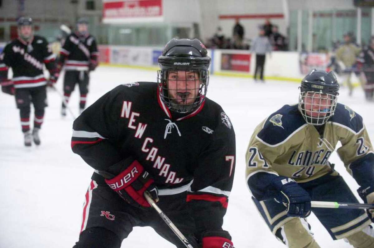 New Canaan's Paul Clemente and Notre Dame's Matt Heim head for the boards as New Canaan and Notre Dame High Schools face off in a boys hockey game at Milford Ice Pavilion in Milford, Conn., January 26, 2012.