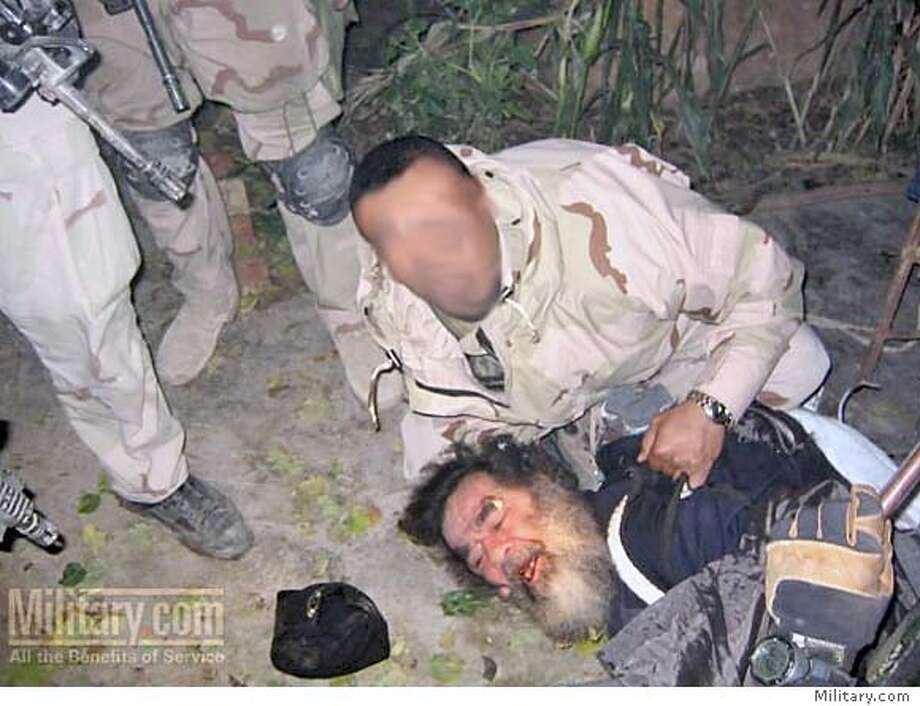 Saddam Hussain (on the ground, lower right) at the moment of his capure, according to the caption on the website Military.com.  Used with permission of Military.com.  for use in a Patrick Hoge.