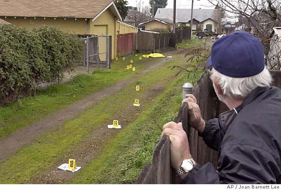 George Newton, right, looks over his neighbor's backyard fence Monday morning, Jan. 10, 2005, at the scene in an alley where Andres Raya was fatally shot late Sunday night. Raya was suspected in the killing of a Ceres police officer and critical wounding of a second officer in a Sunday night shooting, according to Stanislaus County Sheriff's spokesman Jason Woodman. (AP Photo/The Modesto Bee, Joan Barnett Lee) , MAGS OUT, TV OUT, INTERNET OUT Photo: JOAN BARNETT LEE