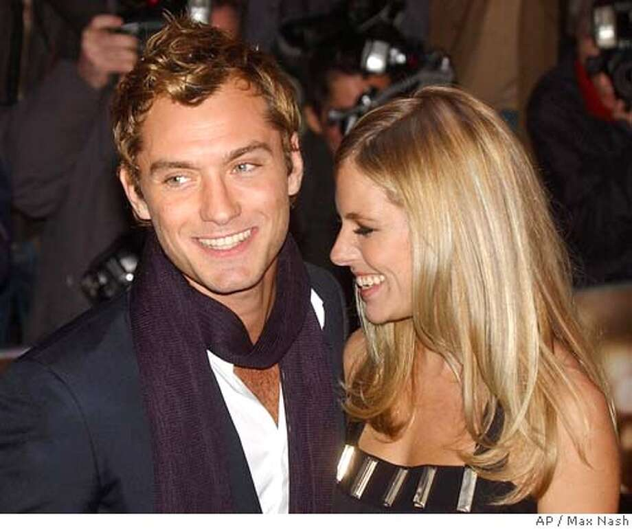 "** FILE ** Actor Jude Law with his co-star and girlfriend Sienna Miller arrive at the world premiere of their latest film, ""Alfie,"" in London's Leicester Square, in this Oct. 14, 2004 file photo. Law has become engaged to Miller after proposing to her on Christmas Day,the couple's spokeswoman said Wednesday Jan. 5, 2005.(AP Photo/ Max Nash) Photo: MAX NASH"