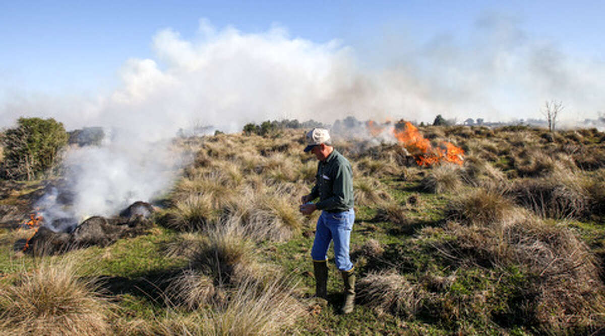 Danny Smith lights a match while helping with a controlled burn on a neighbor's pasture property south east of Bay City.