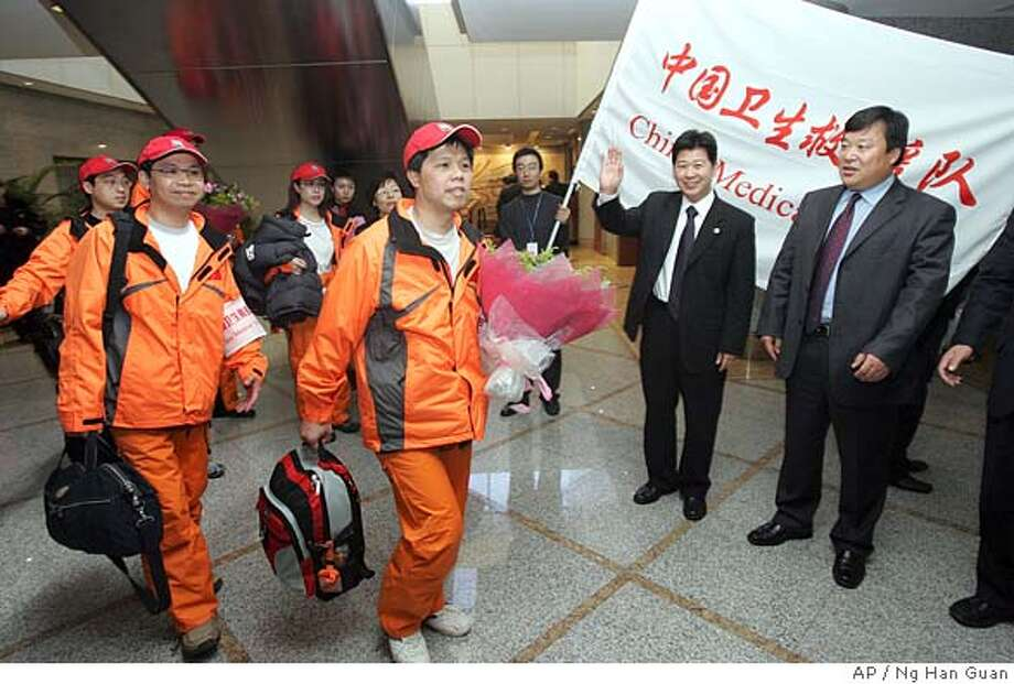 Chinese officials send off a four member Chinese medical team departing for Sri Lanka with medical supplies at the airport in Beijing, China, Friday, Jan 7, 2005. The Chinese government has pledged US$60 million to the Tsunami relief and said it would continue to send emergency relief, help with reconstruction work, provide subsidized loans and help rebuild tourism in affected areas. (AP Photo/Ng Han Guan) Photo: NG HAN GUAN