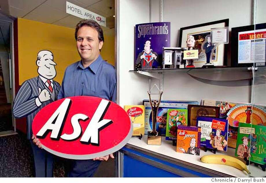"CEO of Ask Jeeves, Steve Berkowitz, holds the lettered sign that says, ""Ask,"" which is part of the Ask Jeeves logo, while standing next to various company awards, Ask Jeeves butler themed items, and the Ask Jeeves butler in background, left, at company headquarters.  7/14/04 in Emeryville  Darryl Bush / The Chronicle Photo: Darryl Bush"