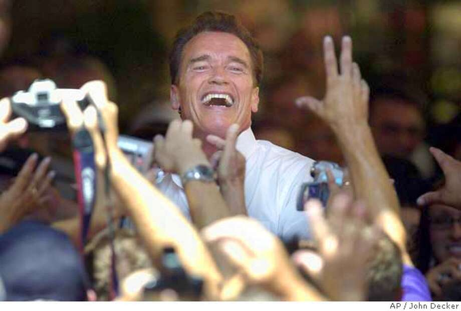 California Gov. Arnold Schwarzenegger smiles as he throws t-shirts to supporters during a rally at Sherwood Mall in Stockton, Calif., Sunday, July 18, 2004. The governor urged those in attendance to contact their legislators and tell them to support his budget proposal. (AP Photo/Sacramento Bee, John Decker) TV OUT, MAGS OUT, ONLINE OUT. MANDIT CREDIT. Photo: JOHN DECKER