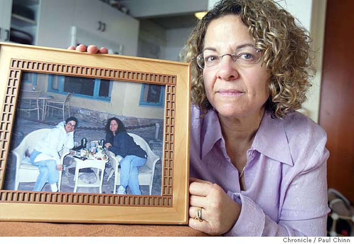 Debe Bloom holds a photograph of herself (in photo, at right) and her twin sister Carol during a birthday trip to Death Valley in February 2000. Debe Bloom hosts a meeting of the Twinless Twins Support Group on 11/13/04 in Pacifica, CA. PAUL CHINN/The Chronicle