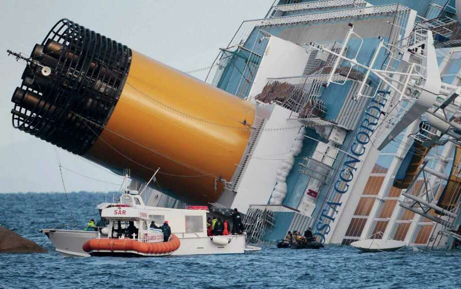 Italian firefighters conduct search operations on the luxury cruise ship Costa Concordia that ran aground the tiny Tuscan island of Isola del Giglio, Italy, Sunday, Jan. 15, 2012. The Costa Concordia cruise ship ran aground off the coast of Tuscany, sending water pouring in through a 160-foot (50-meter) gash in the hull and forcing the evacuation of some 4,200 people from the listing vessel early Saturday, the Italian coast guard said. (AP Photo/Gregorio Borgia) Photo: Gregorio Borgia / AP
