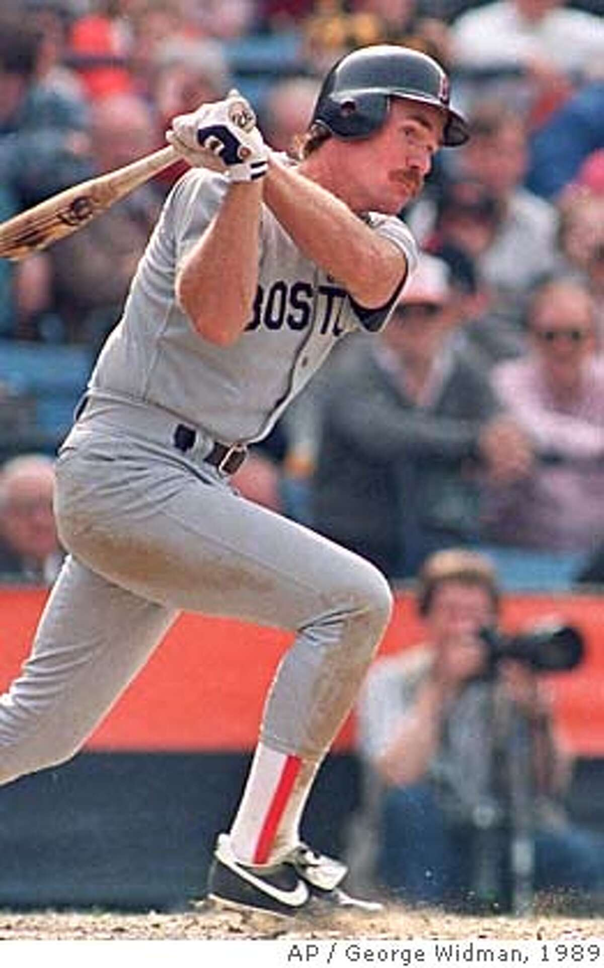 ** FILE ** Boston Red Sox' Wade Boggs follows the flight of his sixth inning double against the Baltimore Orioles in the season opener at Baltimore's Memorial Stadium, in this April 3, 1989 photo. Boggs and Ryne Sandberg were elected to the Hall of Fame Tuesday Jan. 4, 2005. (AP Photo/George Widman)