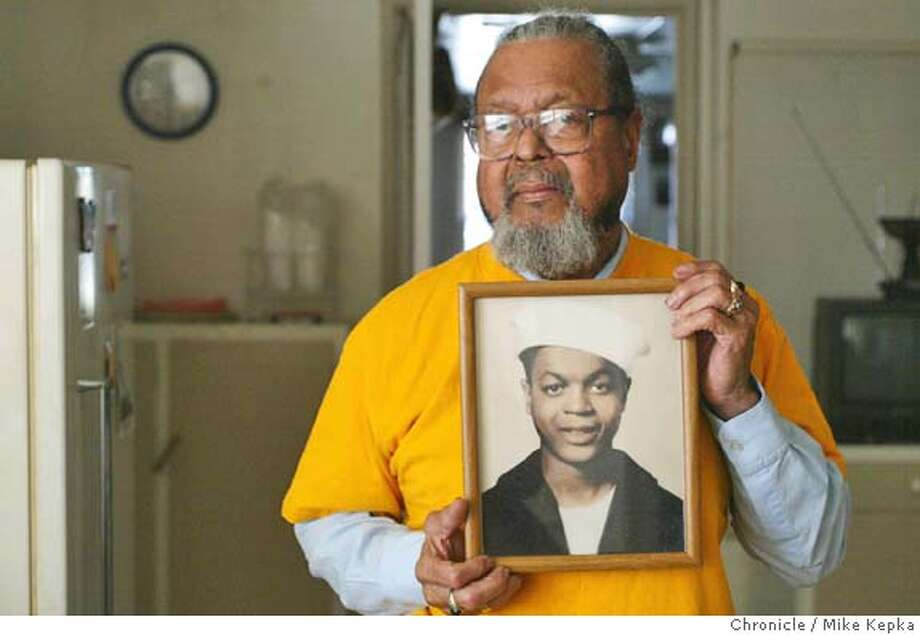 Holding a picture take in his naval uniform when he was 18, Robert Edwards, 78, of Oakland is one of just a few remaining survivors from a large explosion at the Port of Chicago, near what is now Pittsburg, on July 17, 1944. The ammunitions blast killed hundreds of soldiers and wounded as many as 400.  MIKE KEPKA/The Chronicle Photo: MIKE KEPKA
