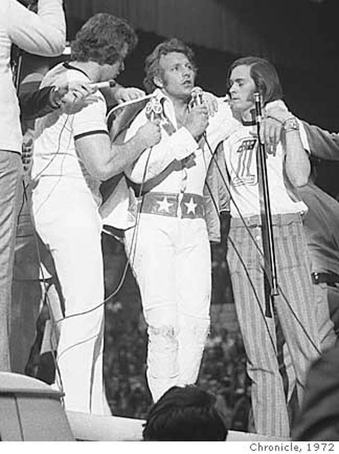 KNIEVEL4-03MAR72-CD-CHRONICLE - Evel Knievel, addresses crowd at the Cow Palace, after making a record 12 car jump with his motorcycle. Chronicle Photo Ran on: 01-05-2005  Evel Knievel objected to &quo;you're never too old to be a pimp'' under a photo of him and two women. Ran on: 01-05-2005  Evel Knievel objected to &quo;you're never too old to be a pimp'' under a photo of him and two women.