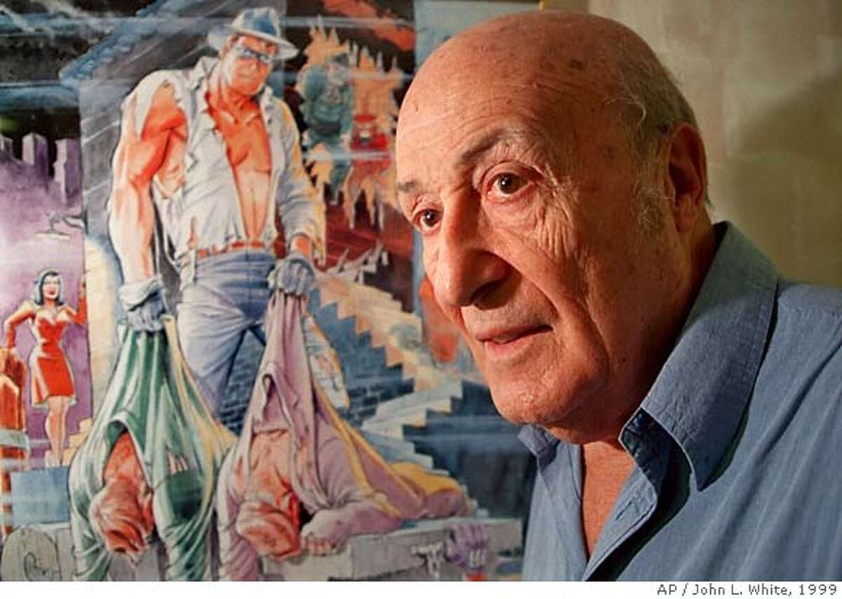 Will Eisner stands next to a poster of