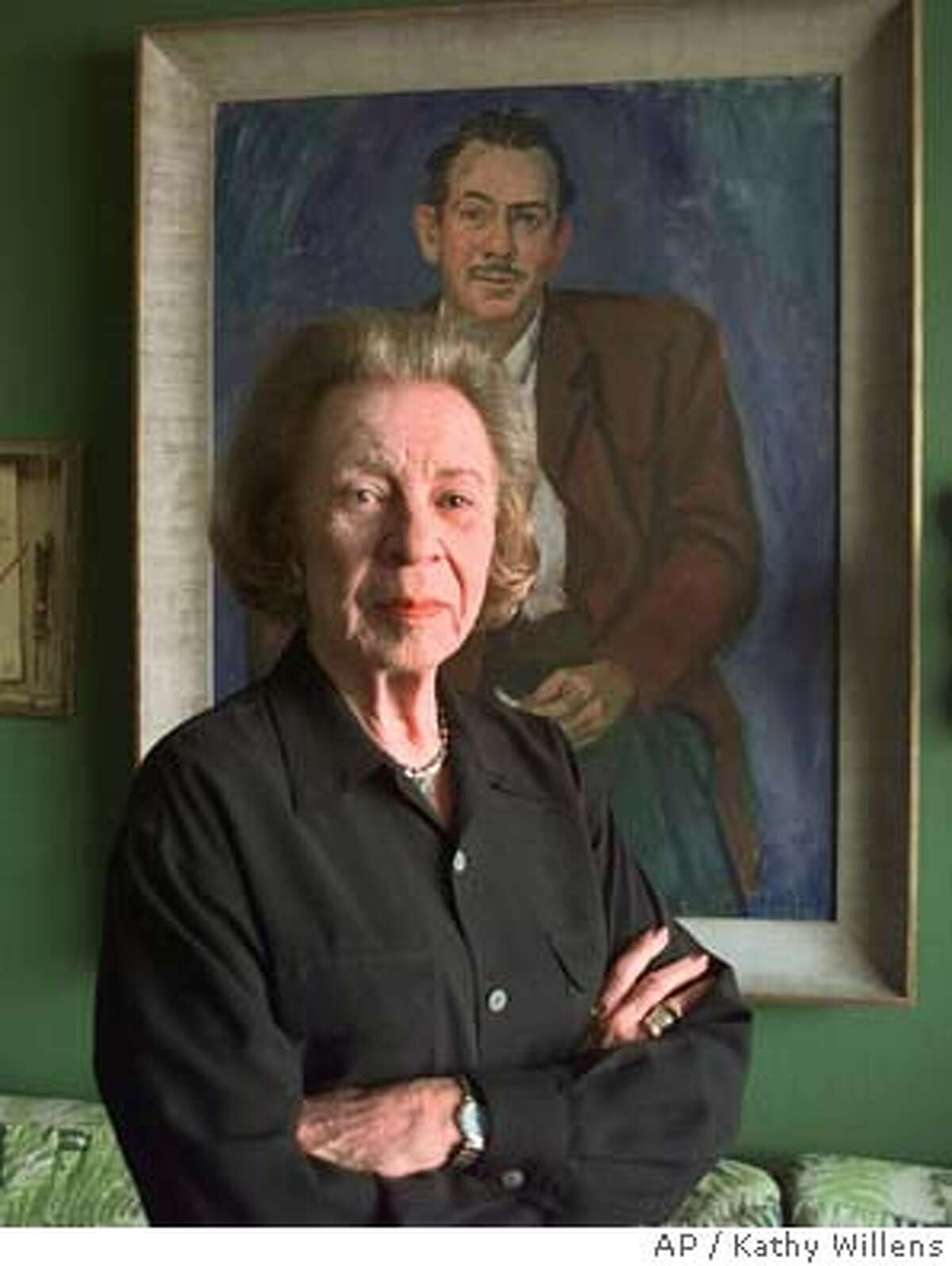 """Elaine Steinbeck poses in front of a painting of her late husband John in the library/study of her New York city apartment in this May 7, 1998 file photo. John Steinbeck's surviving blood heirs are suing the estate of his third wife, Elaine Steinbeck, alleging a """"30-year hidden conspiracy"""" to cheat them of royalties and copyright control and detailing a bitter family feud. The late writer's son, Thomas Steinbeck, and granddaughter, Blake Smyle, filed suit Thursday, July 15, 2004, in the U.S. District Court in New York, seeking greater ownership of """"The Grapes of Wrath"""" and other Steinbeck classics and monetary damages of at least $18 million. (AP Photo/Kathy Willens, File) MAY 7, 1998 FILE PHOTO"""