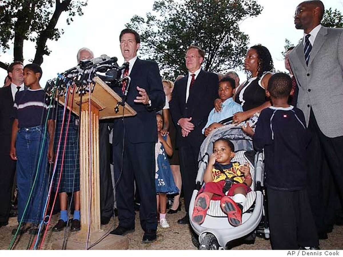 Senator Sam Brownback, R-Kan., talks to reporters on Capitol Hill Wednesday, July 14, 2004, after republicans lost in their attempt to amend the consitution to ban . Supporters of the amendment stand behind Brownback. (AP Photo/Dennis Cook)
