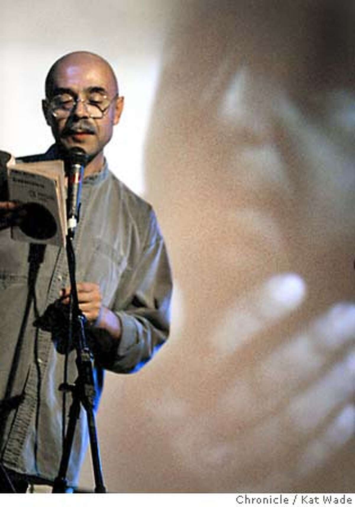 As photos of the poet Pablo Neruda flash on the screen behind, Ivan Herrera reads his poems aloud during the all day celebration of Pablo Neruda's centennial birthday with poetry readings and an artistic tribute to the poet born on July 12, 1904 at La Pe�a Cultural Center in Berkeley on 7/11/04. The Chronicle/ Kat Wade