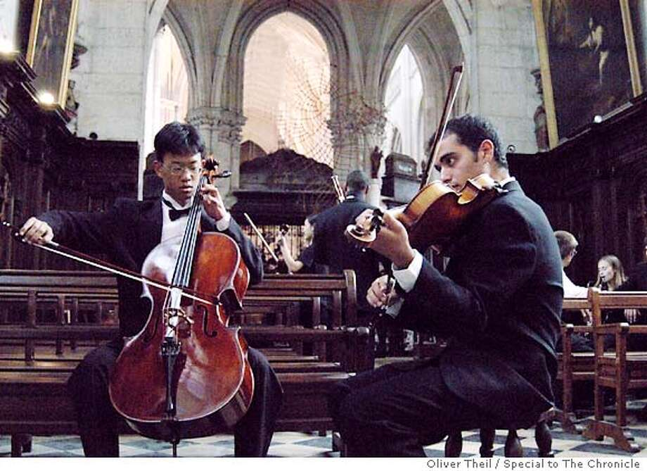 SF Symphony Youth Orchestra members Paul Hyun and Beeri Moalem warming up in the 17th century L'abbaye de St-Riquier on tour in northern France.