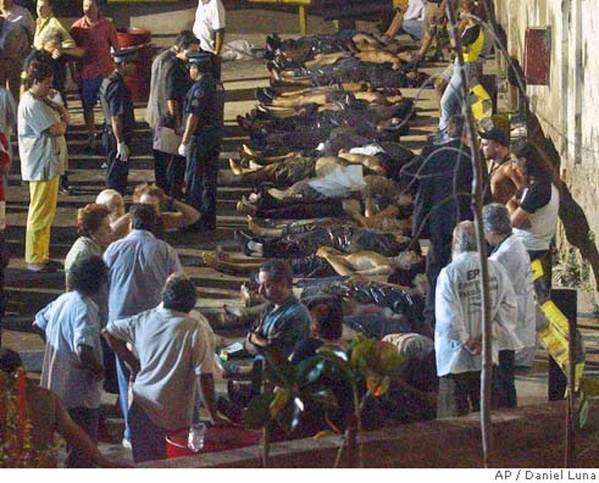 Bodies waiting to be transferred to a local morgue are lined up in a parking area outside a nightclub in Buenos Aires, Argentina, Friday, Dec. 31, 2004. The fire swept through the crowded nightclub, killing at least 149 people and injuring more than 300, officials said Friday. The blaze broke out during a rock concert at a popular nightclub. (AP Photo/Daniel Luna)