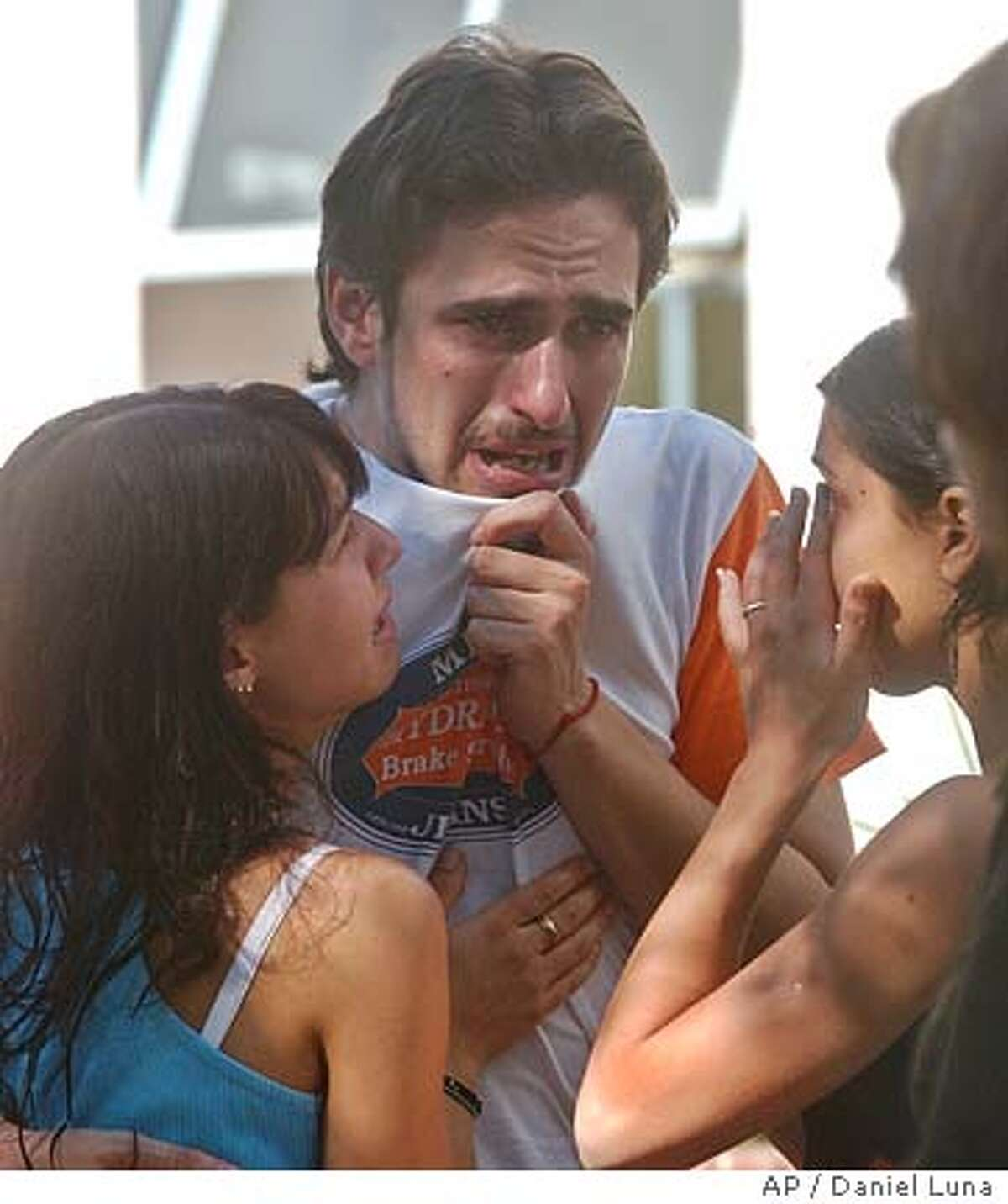 Grieving family members react after finding their loved ones in the morgue of a local hospital, 175 people were killed and more than 600 injured when a fire swept through a crowded nightclub in Buenos Aires, Argentina, Friday, Dec. 31, 2004. Several survivors said they saw a flare hit a foam lining on the roof of the concert hall, triggering a fire. (AP Photo/Daniel Luna)