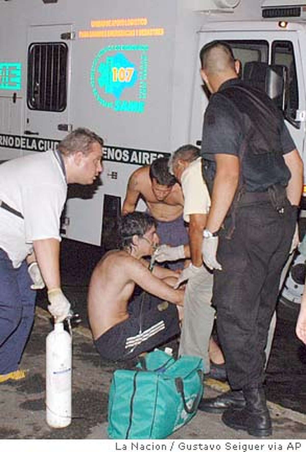 People injured in a nightclub fire are helped outside the nightclub in Buenos Aires, Argentina, Friday, Dec. 31, 2004. The fire swept through the crowded nightclub, killing at least nine people and injuring more than 200, police said Friday. The blaze broke out during a rock concert at a popular nightclub. (AP Photo/La Nacion, Gustavo Seiguer) **Buenos Aires Out**