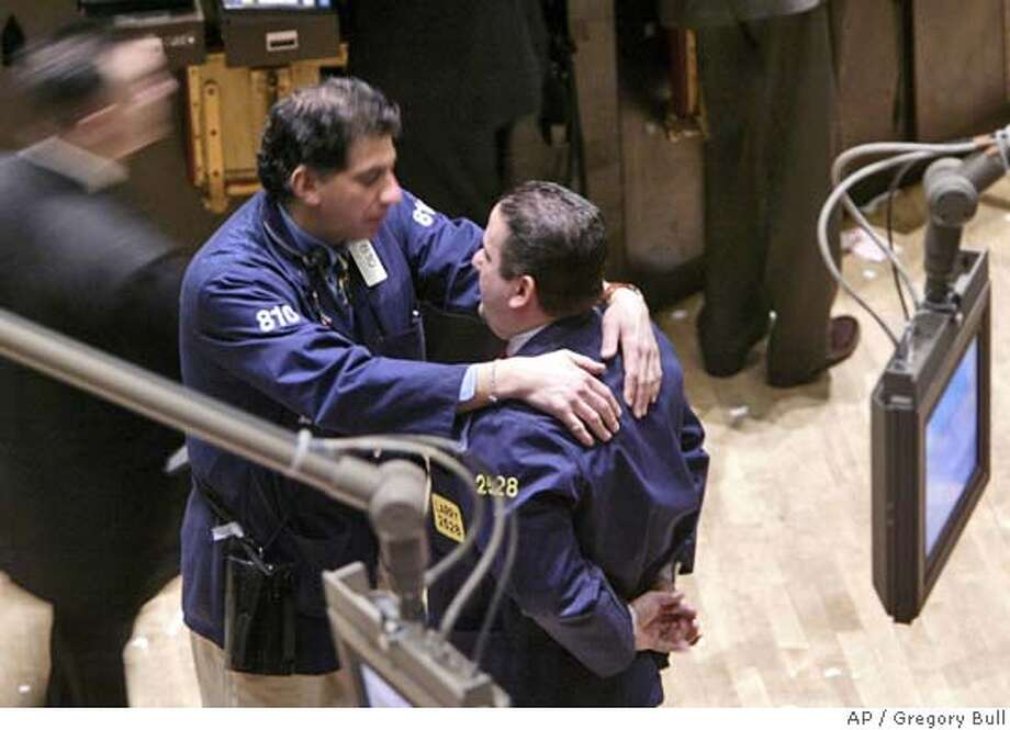 Traders talk on the floor of the New York Stock Exchange on the last day of the year Friday, Dec. 31, 2004. As of mid-morning, activity looked light on the trading floor for the year's last trading day. Stocks edged higher in light New Year's Eve trading Friday as Wall Street prepared to end the year with solid gains. (AP Photo/Gregory Bull) Photo: GREGORY BULL