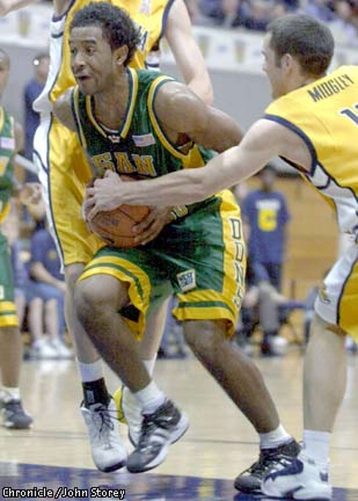 CAL-C-30DEC02-SP-JRS-The Cal Bears vs. the USF Dons at Haas Pavillion in men's basketball. Richard Midgley of Cal puts his hand on the ball to stop John Cox of USF in the first half. Chronicle photo by John Storey