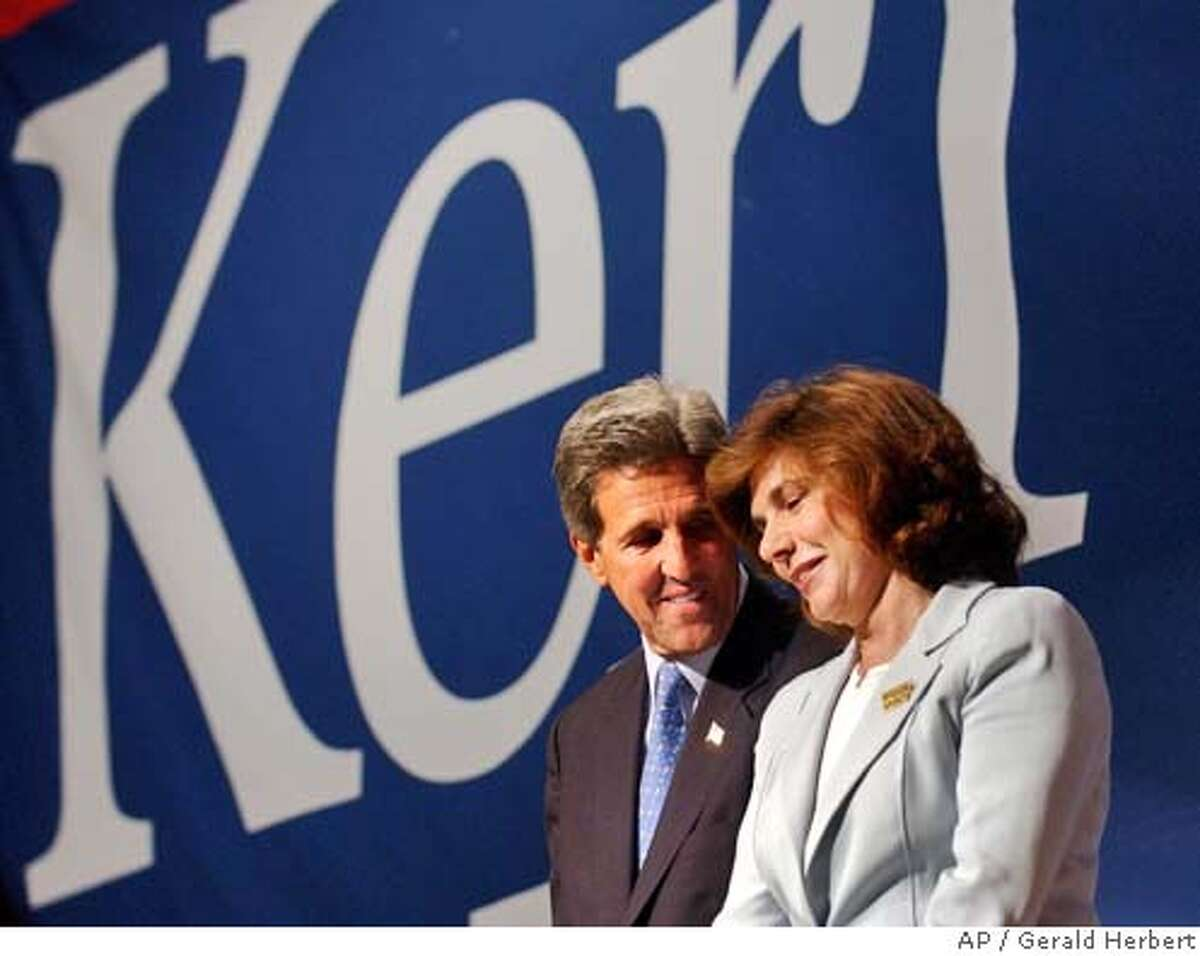 Democratic presidential candidate Sen. John Kerry, D-Mass., smiles at his wife Teresa Heinz before she speaks at the 'Women Investing in Change' luncheon in Boston Mass., Monday, July 12, 2004. (AP Photo/Gerald Herbert)