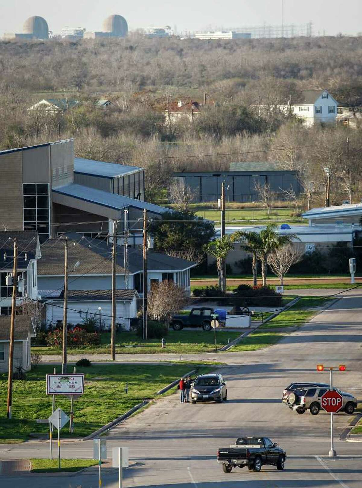 The South Texas Project Electric Generating Station looms beyond Matagorda's main intersection Thursday. The tiny coastal town had been counting on an expansion of the nuclear plant, but it has stalled.