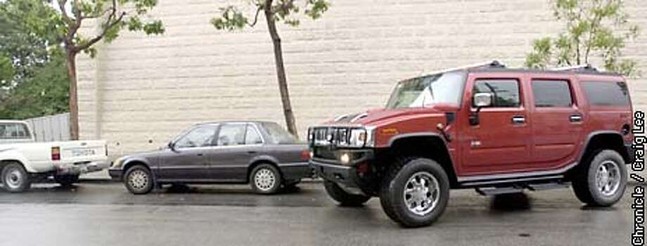 Photo of the Hummer parallel parking next to some smaller cars. Story on the popularity of the Hummer vehicle. It weighs more than three tons and is one of the least fuel efficient cars on the road. It can scale a 60 percent incline, ford small lakes, climb fallen logs and traverse boulders. General Moters is selling as many of the $50, 000 Hummer 2 urban tanks as it can make.  Photo by Craig Lee Photo: CRAIG LEE