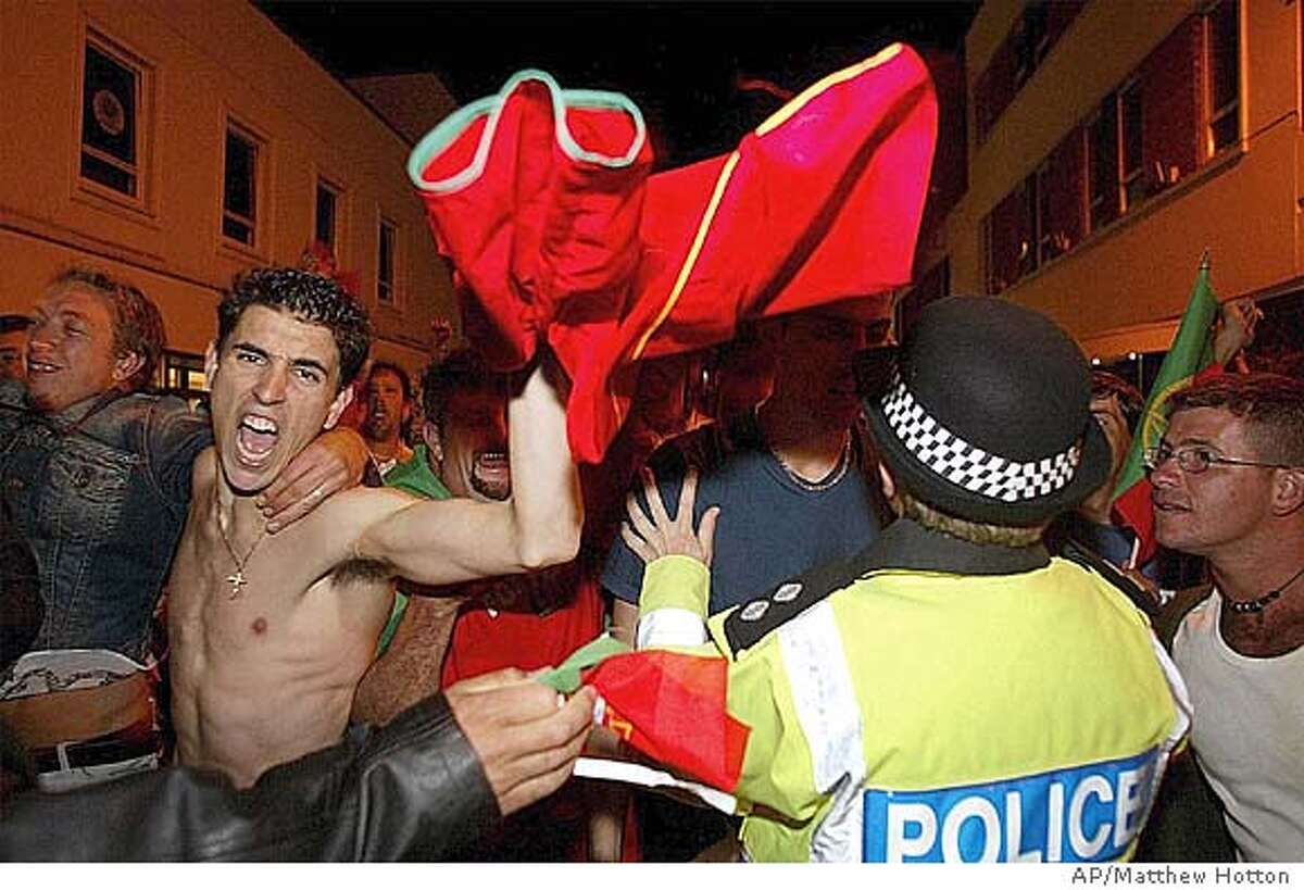 A fan with a Portuguese soccer shirt celebrates as Police talk to other fans during clashes in the Channel Island of Jersey, England, Thursday, June 24, 2004, where Police used CS gas to disperse a crowd of 1,500 England supporters who taunted members of the island's large Portuguese community after the Euro 2004 quarter final Thursday. England lost to the home nation after a penalty shoot-out at the end of extra time. (AP Photo/PA, Jersey Evening Post, Matthew Hotton) ** UNITED KINGDOM OUT NO SALESMAGS OUT INTERNET OUT TV OUT ** UNITED KINGDOM OUT MAGS OUT INTERNET OUT TV OUT