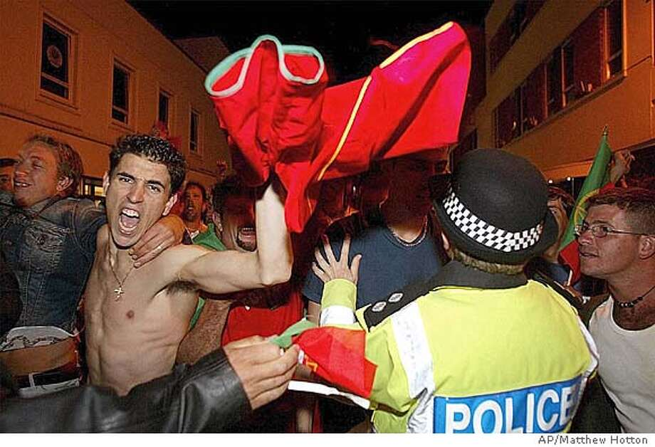 A fan with a Portuguese soccer shirt celebrates as Police talk to other fans during clashes in the Channel Island of Jersey, England, Thursday, June 24, 2004, where Police used CS gas to disperse a crowd of 1,500 England supporters who taunted members of the island's large Portuguese community after the Euro 2004 quarter final Thursday. England lost to the home nation after a penalty shoot-out at the end of extra time. (AP Photo/PA, Jersey Evening Post, Matthew Hotton) ** UNITED KINGDOM OUT NO SALESMAGS OUT INTERNET OUT TV OUT ** UNITED KINGDOM OUT MAGS OUT INTERNET OUT TV OUT Photo: MATTHEW HOTTON