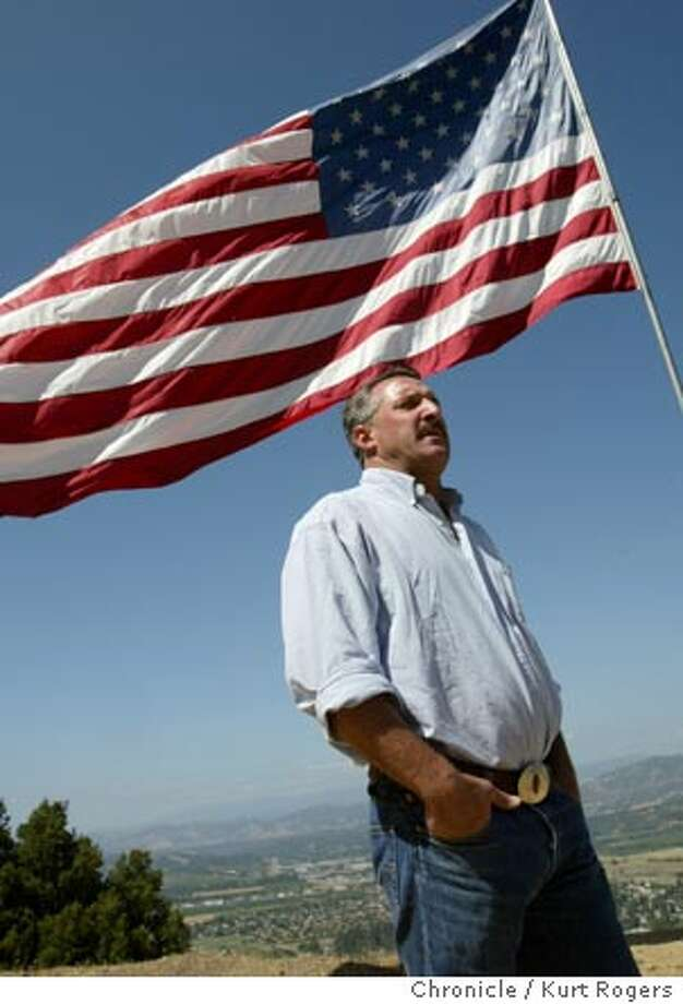 """Ric Piffero overlooking the town of Ukiah and his 25 foot flag.  Ric Piffero thought he was being a true patriot when he set up some loudspeakers from a hillside above Ukiah on the Fourth of July and began belting out the """"Star-Spangled Banner"""" and Springsteen's """"Born in the USA."""" But not everyone appreciated the gesture, most notably a nurse in the valley below who called police and signed a citation accusing Piffero of disturbing the peace 7/8/04 in Ukiah,CA.  Kurt Rogers/The Chronicle Photo: Kurt Rogers"""