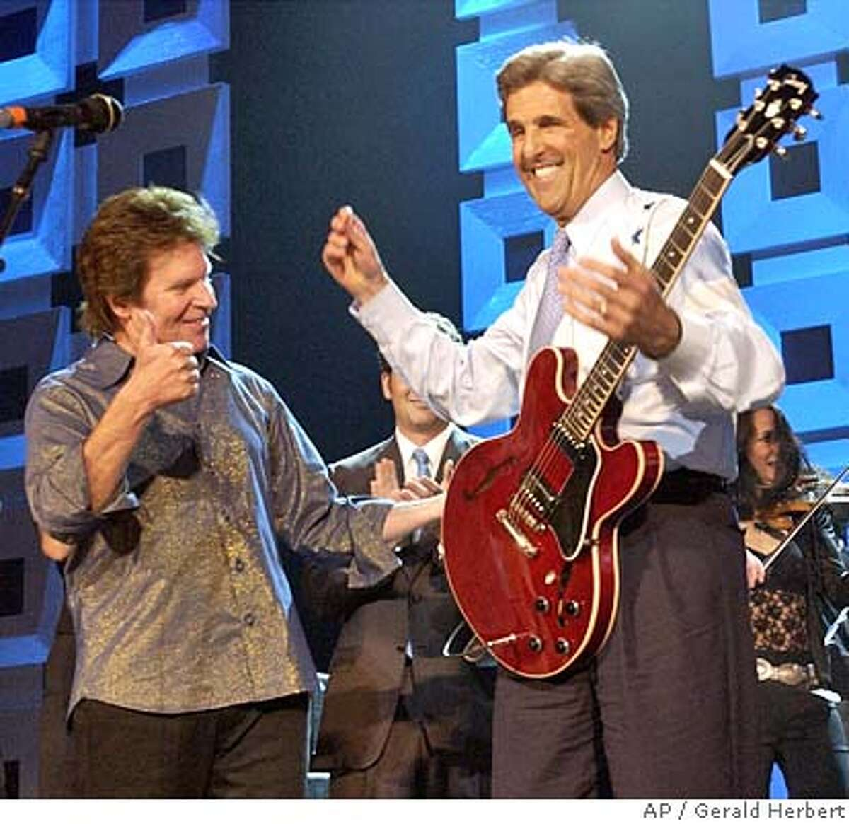 Rocker John Fogerty reacts after Democratic presidential candidate Sen. John Kerry, D-MA, played the guitar during a concert benefiting his campaign at Radio City Music Hall in New York Thursday, July 8, 2004. (AP Photo/Gerald Herbert)