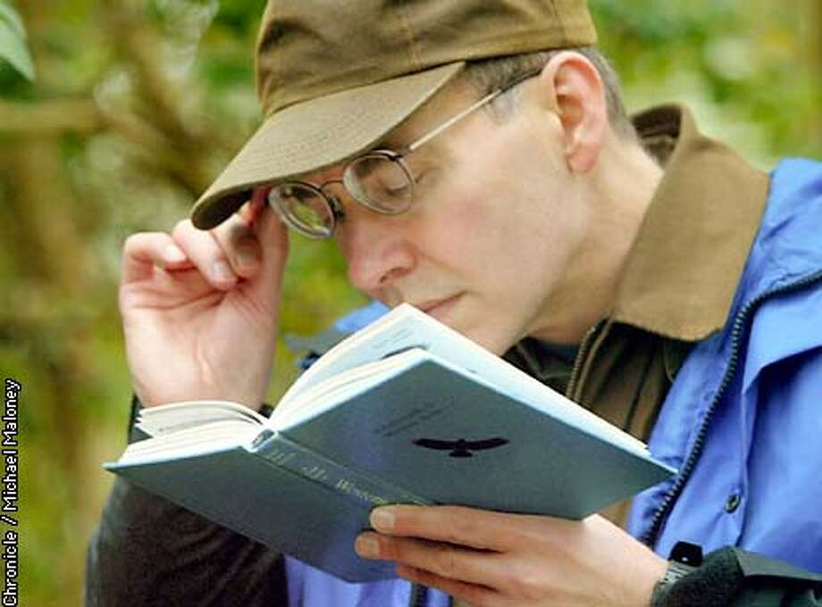 a5dcdb92178 Bird counter Casey Bazewick looks in his bird identification book to  confirm a sighting. We
