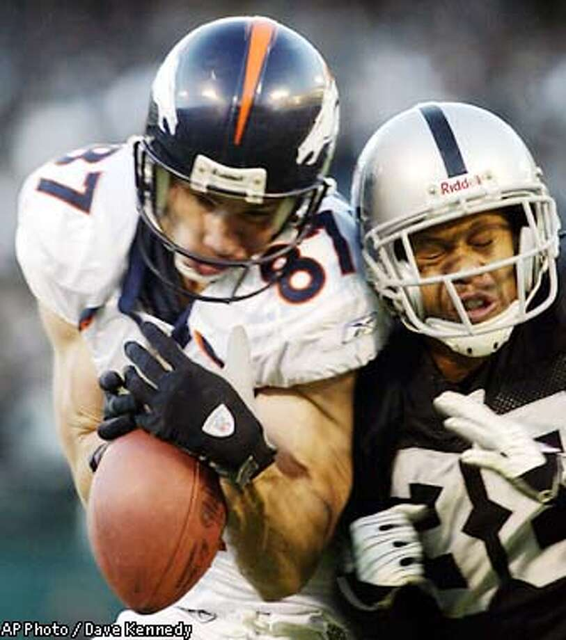 Denver Broncos Ed McCaffrey and Oakland Raiders Clarence Love collide, knocking the ball from the grasp of McCaffrey in Oakland, Sunday, Dec. 22, 2002. Oakland won the game 28-16 over Denver. (AP Photo/Dave Kennedy) Photo: DAVE KENNEDY