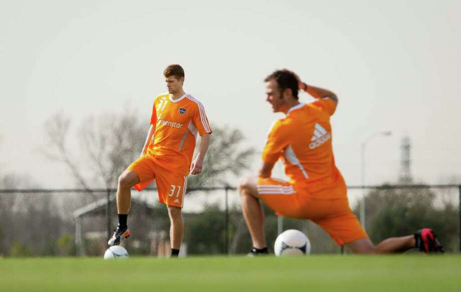 Houston Dynamo defender Andre Hainault, left, and midfielder Brad Davis, right, practice during the Dynamo's first training session of the 2012 season at Houston Amateur Sports Park's Methodist Champions Field on Monday, Jan. 23, 2012, in Houston. The Dynamo will open their season on February 24 against Sporting Kansas City. Photo: Andrew Richardson, For The Chronicle / © 2012 Andrew Richardson